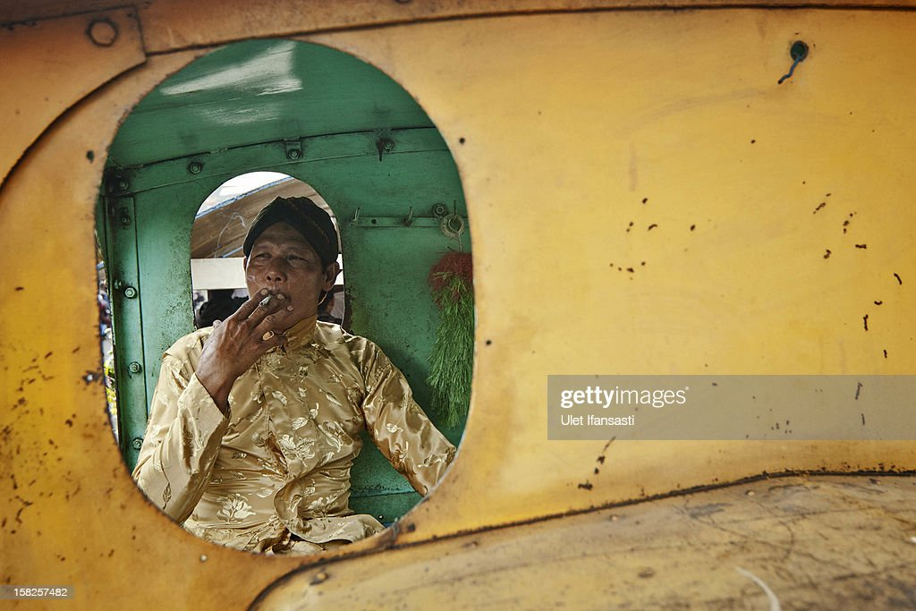 A man smokes in a lorry locomotive during a mass wedding ceremony on December 12, 2012 in Yogyakarta, Indonesia. Twelve couples participated in a mass wedding as today saw a surge in marriage across the globe to mark the once in a century date of 12/12/12.
