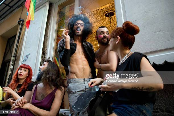 A man smokes in front of a hairdresser in the Chueca neighborhood during the Madrid Gay Pride Festival 2013 on July 5 2013 in Madrid Spain According...