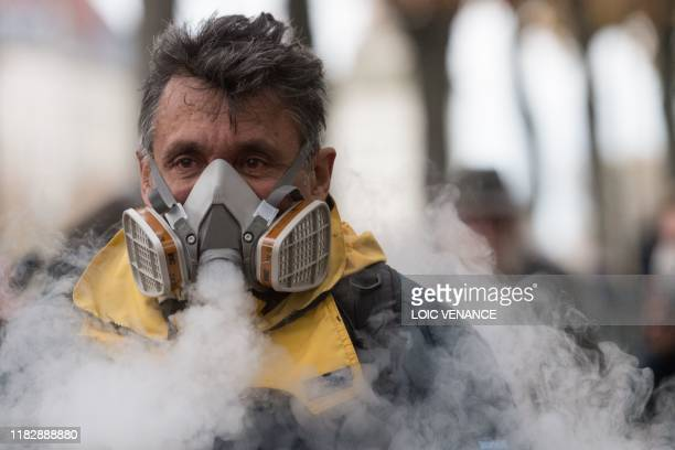 A man smokes in his gas mask during a demonstration marking the first anniversary of the yellow vest movement on November 16 in Nantes western France...