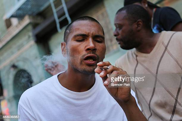 """Man smokes K2 or """"Spice"""", a synthetic marijuana drug, along a street in East Harlem on August 5, 2015 in New York City. New York, along with other..."""