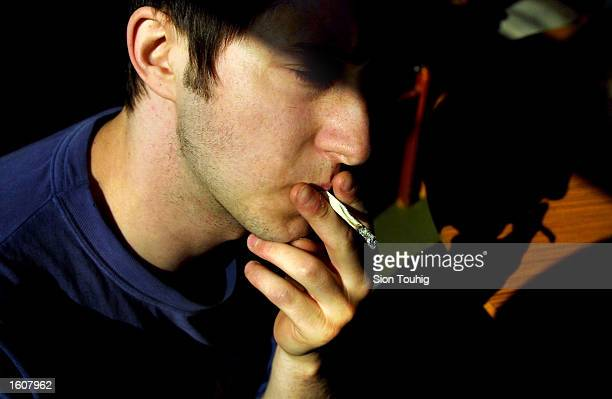 A man smokes marijuana at his home August 8 2001 in the Dalston section of East London Cannabis use in the United Kingdom is still illegal but it''...