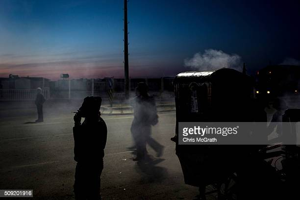 A man smokes next to a street cart selling tea at the closed Turkish border gate on February 9 2016 in Kilis Turkey According to Turkish officials...