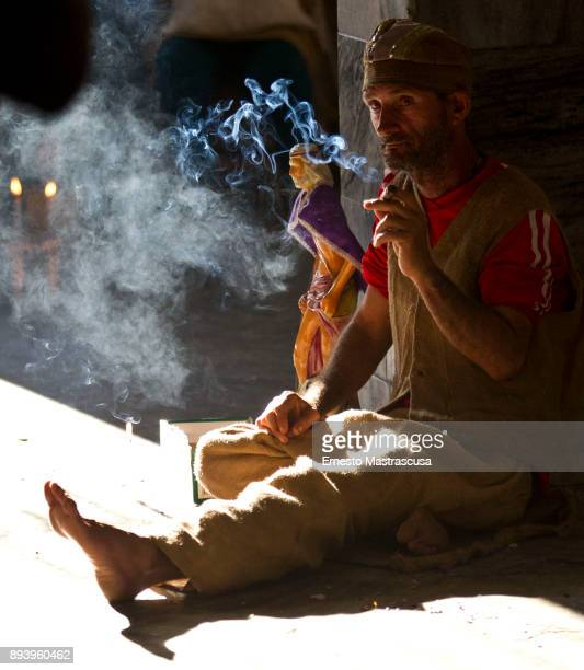 A man smokes next to an image of San Lazaro on December 16 2017 in La Habana Cuba Thousands of believers gather at the Shrine of San Lazaro on the...