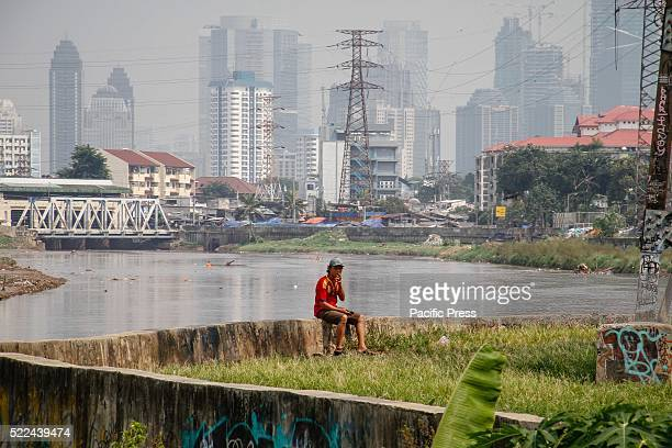 A man smokes on the riverbank as high rise buildings are seen in the background