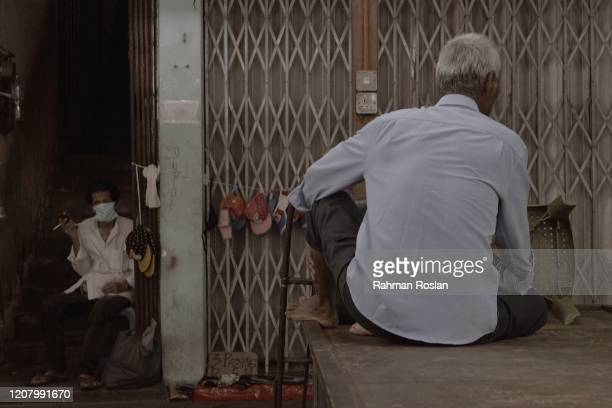 A man smokes under the stairs of a housing complex during Movement Control Order on March 23 2020 in Kuala Lumpur Malaysia Prime Minister Tan Sri...