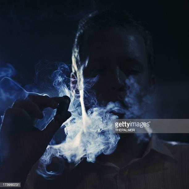 Homem Fumando um charuto no escuro