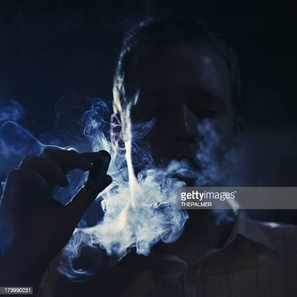 man smoking a cigar in the dark