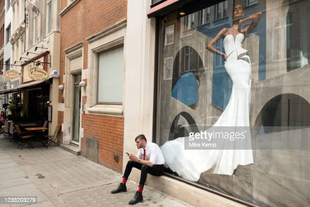 Man smoking a cigarette and looking at his smartphone as he sits outside a bridal wear shop on Bond Street on 25th May 2021 in London, United...