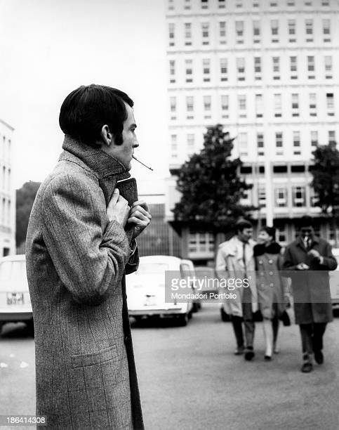 A man smoking a cigarette looking annoyed at some colleagues walking hugged Italy 1968
