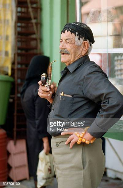 Man Smoking a Pipe and Holding Amber Worry Beads