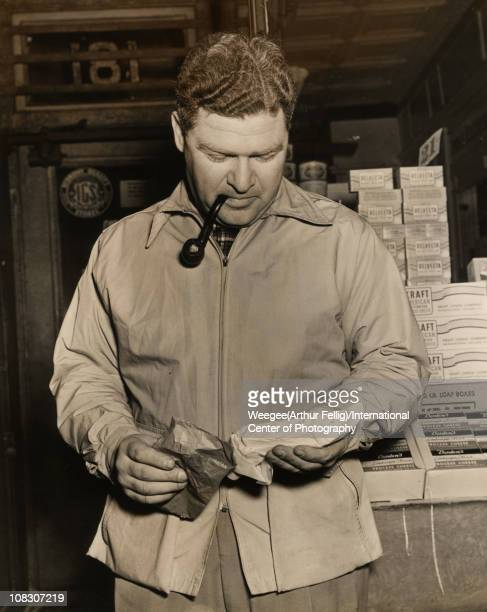 A man smoking a pipe holds two packages in front of a diary store March 1943 Stacks of Velveeta Kraft and Borden processed cheeses are visible behind...