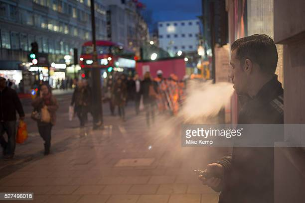 Man smoking a vaporizer on Oxford Street in central London UK Britiains busiest shopping district Electronic cigarettes are batterypowered vaporizers...