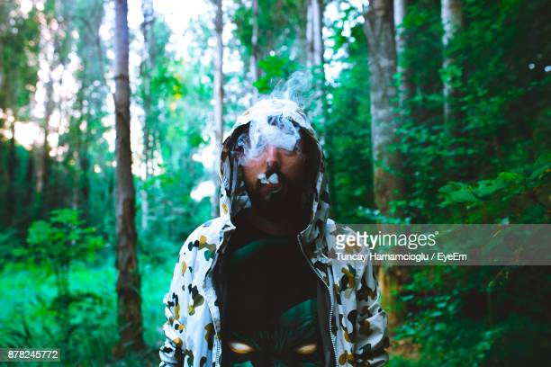 Man Smoking Against Trees In Forest