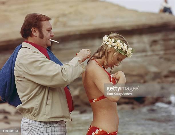 Man smoking and tying bikini knot for woman