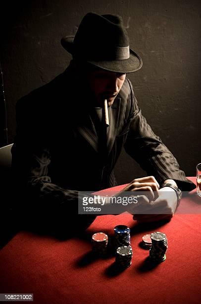 Man Smoking Cigar at Card Table with Poker Chips