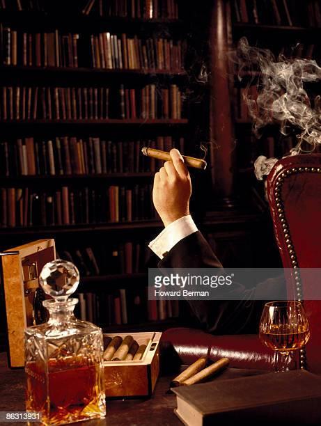 Man smoking cigar in library