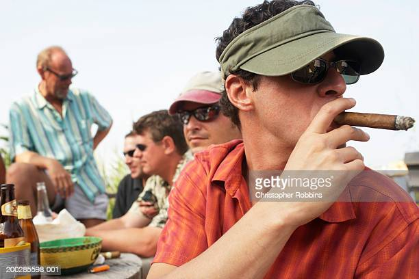 Man smoking cigar sitting with friends around table outdoors