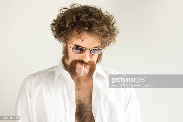 man smoking cigarette against white background - hairy chest stock-fotos und bilder