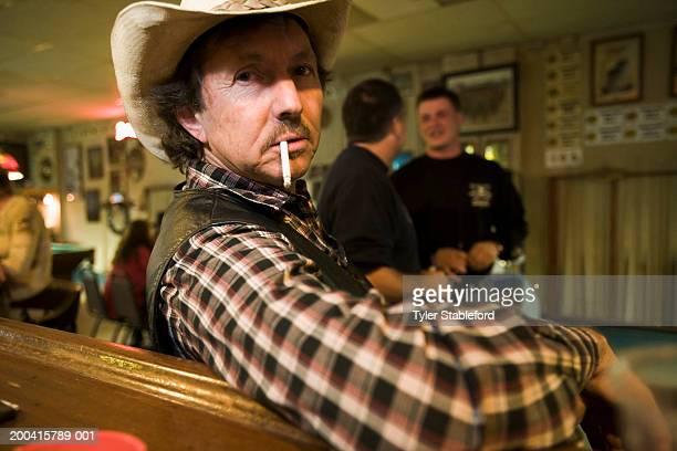 Man smoking cigarette in bar, wearing cowboy hat