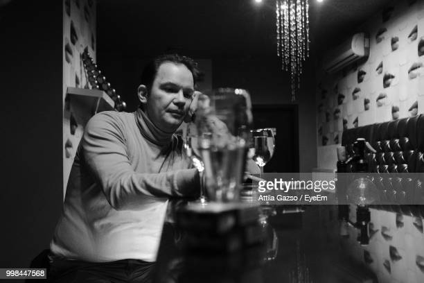 man smoking cigarette while having drink at table in bar - ハンガリー ストックフォトと画像