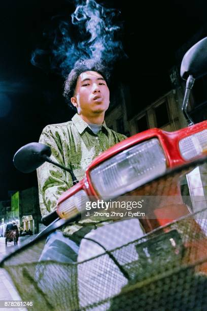 Man Smoking Cigarette While Riding Motorcycle On Road