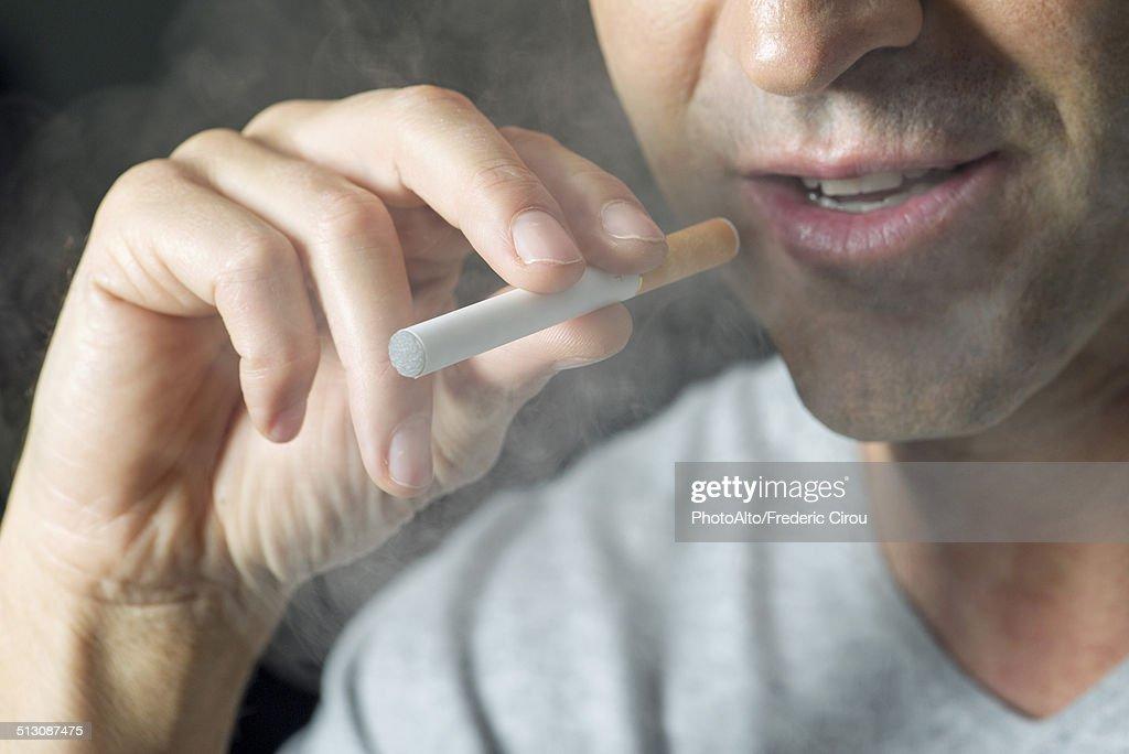 Man smoking electonic cigarette, cropped : Stock Photo