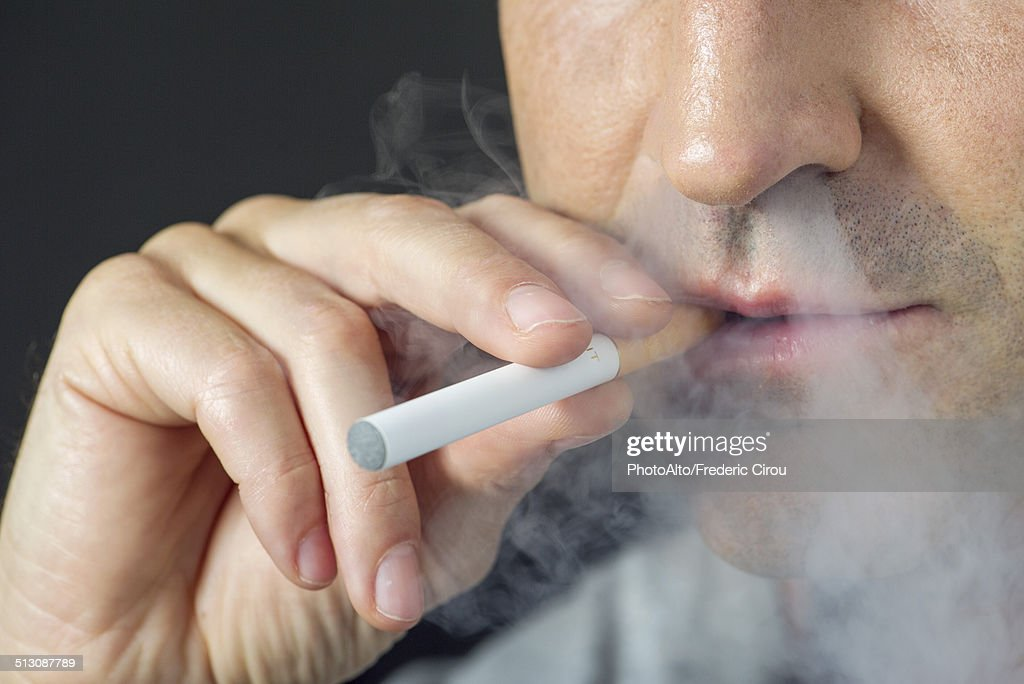Man smoking electonic cigarette, cropped : Stock Photo