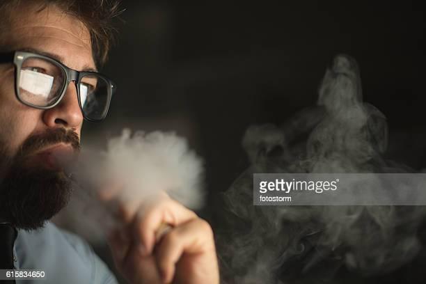 man smoking electonic cigarette - reflexo efeito de luz - fotografias e filmes do acervo