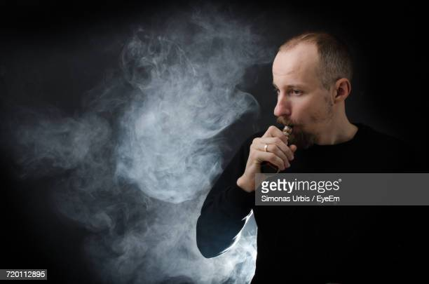 Man Smoking Electronic Cigarette Against Black Background