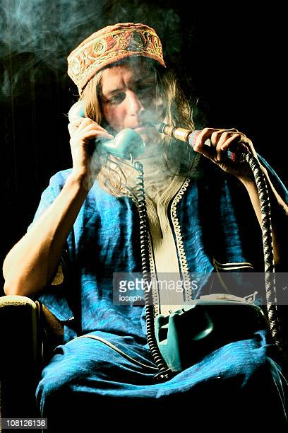 man smoking hookah and talking on phone - hookah stock photos and pictures