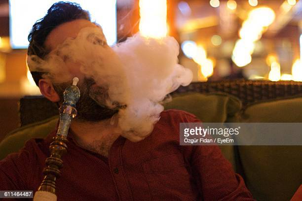 Man Smoking Hookah While Sitting At Restaurant