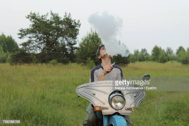 Man Smoking Hookah While Sitting On Motorcycle At Field