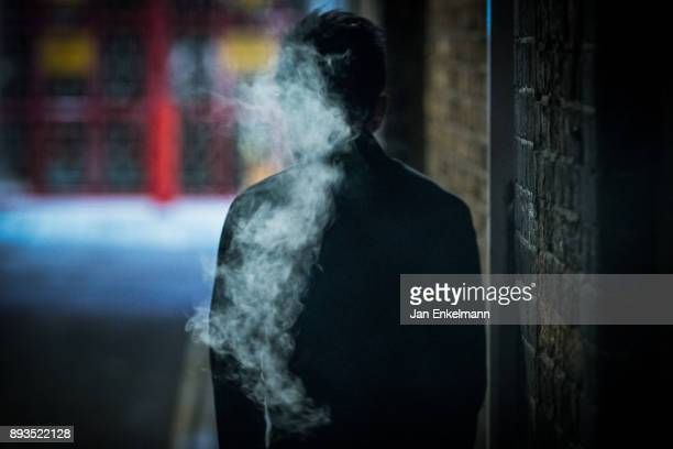 man smoking in a dark alleyway - crimine foto e immagini stock