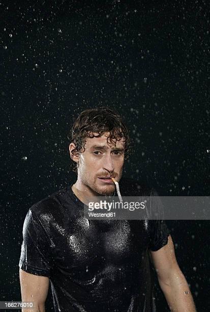 man smoking in rain, portrait. - 濡れている ストックフォトと画像