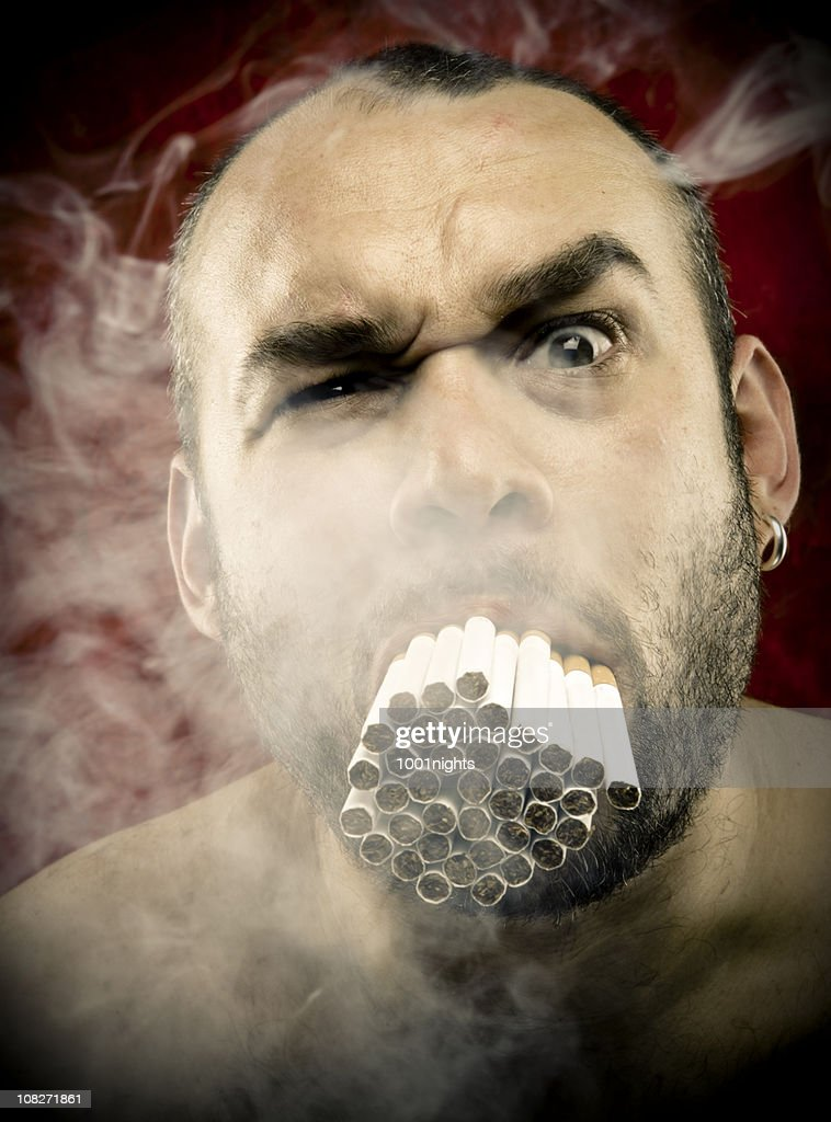 Man Smoking Many Cigarettes in his Mouth : Stock Photo