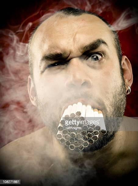 man smoking many cigarettes in his mouth - ugly bald man stock photos and pictures