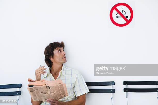Man Smoking near No Smoking Sign