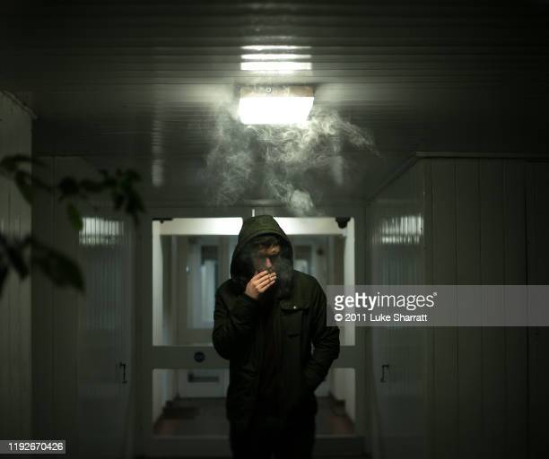 man smoking outside wearing hood - liga bildbanksfoton och bilder