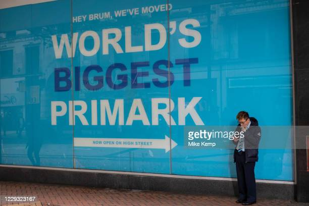 Man smoking while looking at his smart phone beside a large advert for Primark in Birmingham, United Kingdom. The Birmingham store is the biggest...