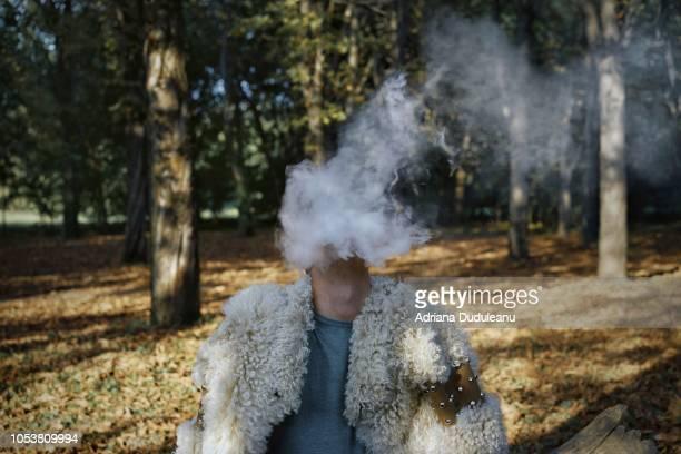 man smoking while sitting in forest - hombre peludo fotografías e imágenes de stock