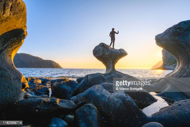man snapping pictures at sunset from the top of kannesteinen rock, norway - rock formation stock pictures, royalty-free photos & images