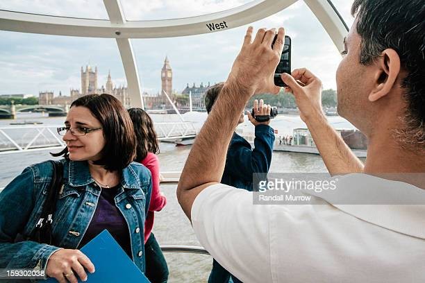 Man snaps a photo of Big Ben with his iPhone as he and his companions enjoy a ride on the London Eye.