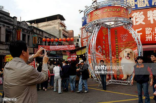 A man snaps a picture of his wife posing in front of a large symbol of a dog According to the chinese calendar and astrology the coming year will be...