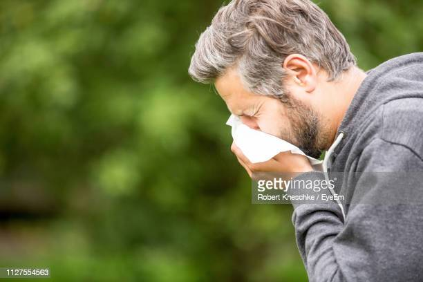 man sneezing by tree - tree man syndrome stock photos and pictures