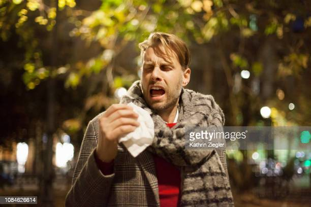 man sneezing, holding facial tissue - sneezing stock pictures, royalty-free photos & images