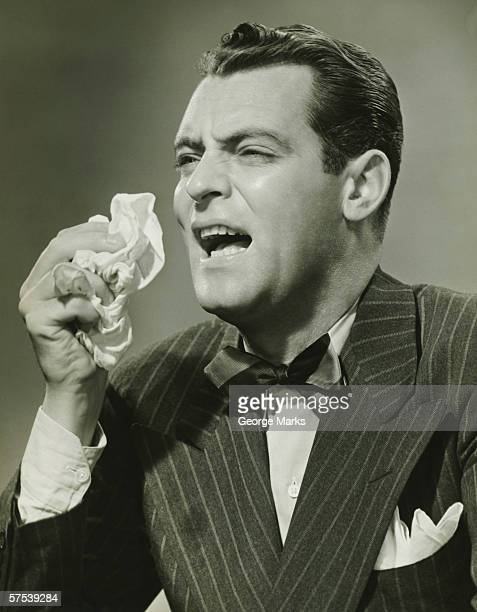 Man sneezing in studio, (B&W)