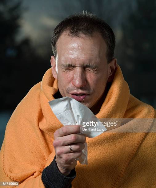 Man sneezing on tissue