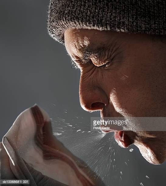 Man sneezing on tissue