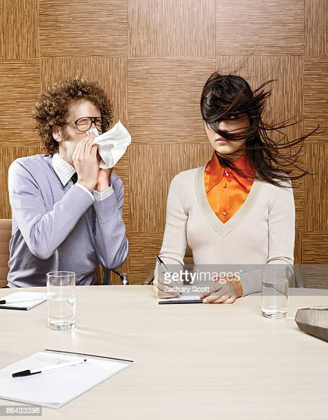 Man sneezing on woman in office environment