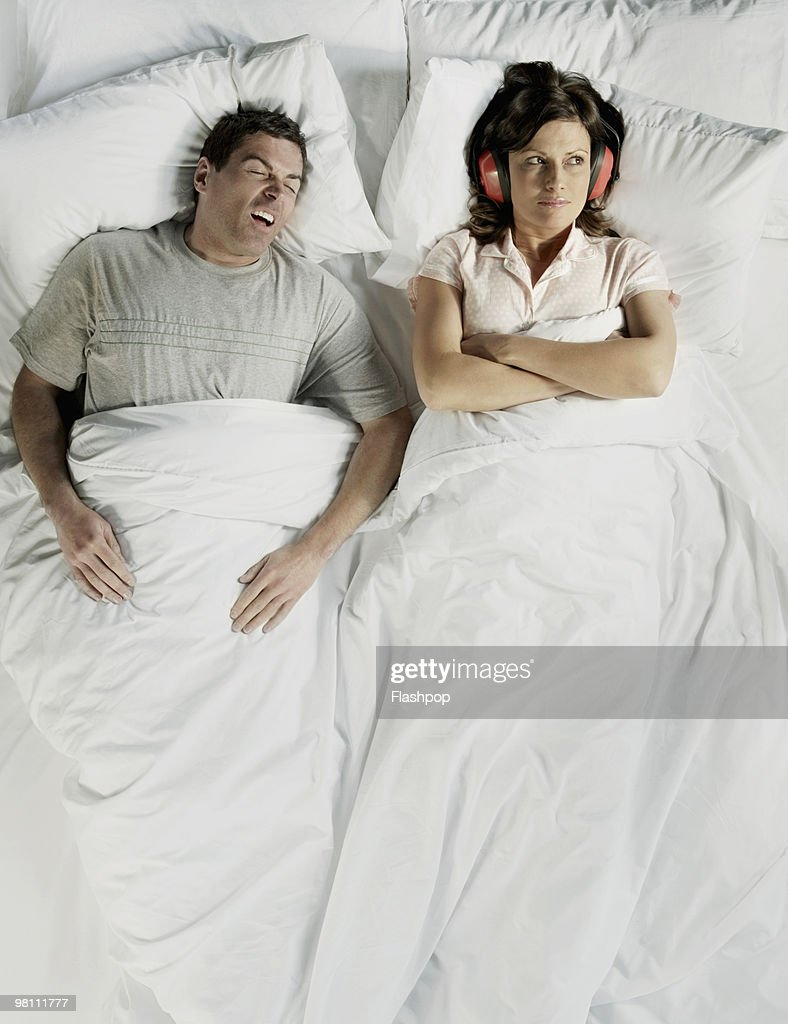 Man snoring in bed with woman wearing ear defender : Stock Photo